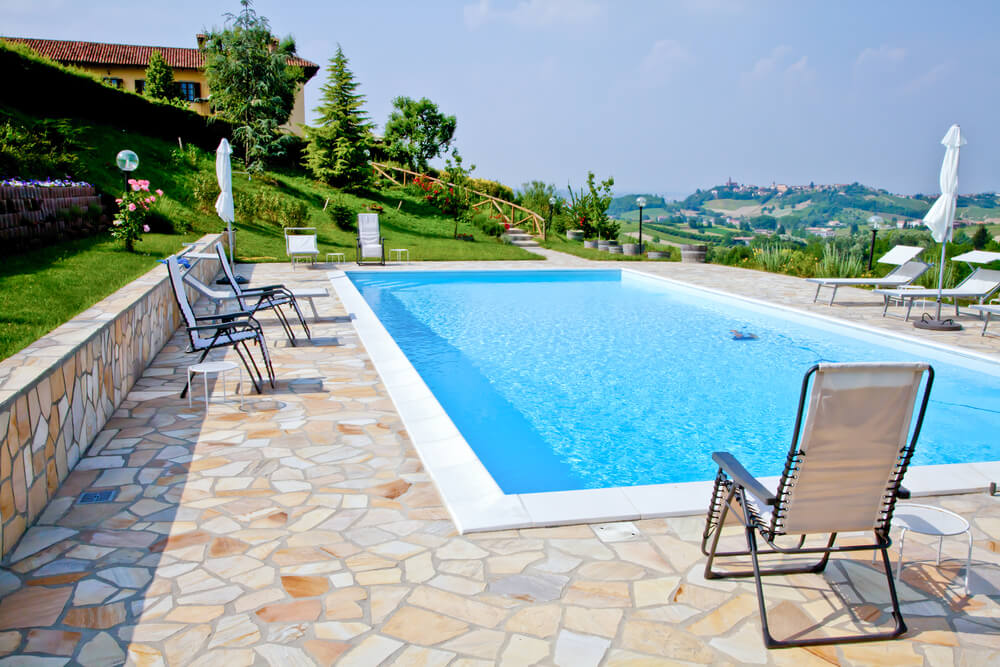 Large rectangle pool with flagstone patio on sloped for Pool design sloped yard