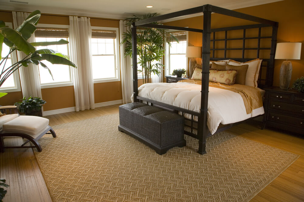 This Master Bedroom Features A Bamboo Style Four Poster Bed Black Wicker Ottoman And A Modern