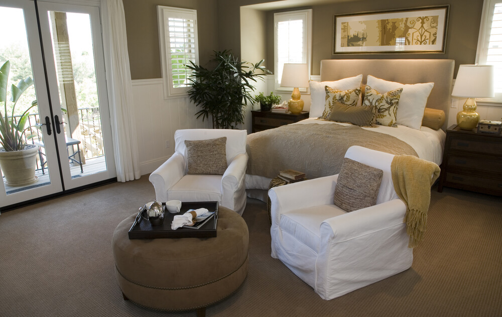 Bedroom Featuring White On Tan Bed Set And Chairs In A