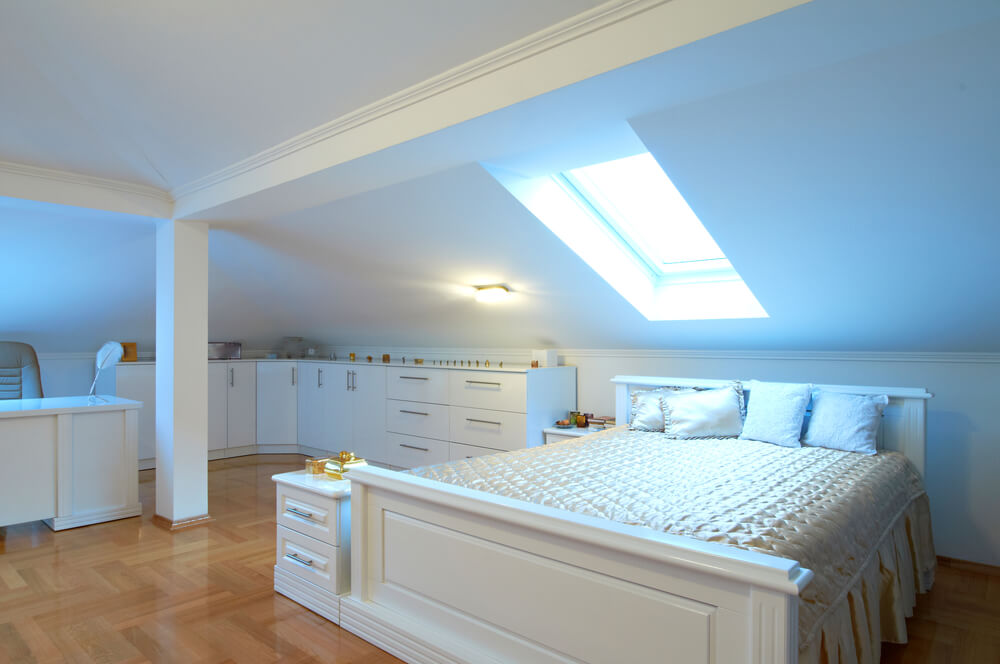 attic bedroom with sloping ceiling built in dresser drawers and