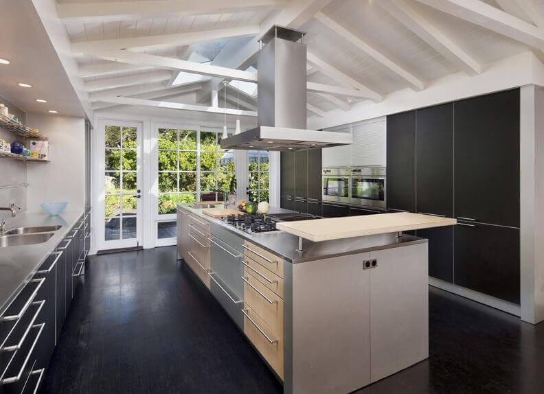 High contrast between black flooring and cabinetry, and white walls and vaulted ceiling with exposed beams in this well-lit kitchen. Large island features range and sink along with serving space.