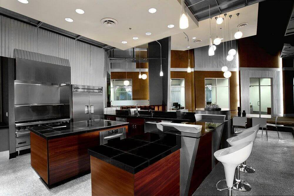 Rich wood tones and black countertops center this modern industrial-look kitchen, featuring metallic flooring, walls, and appliances under drop ceiling with embedded and hung lighting.