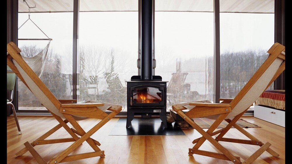 Head on view of black heating stove, seated centrally against the back patio doors over hardwood flooring.