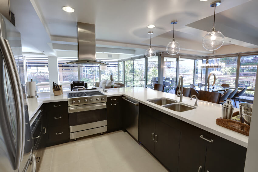 Compact kitchen area sits within large open space in this home. Black cupboards with white countertops are lit by embedded and hung glass lighting.