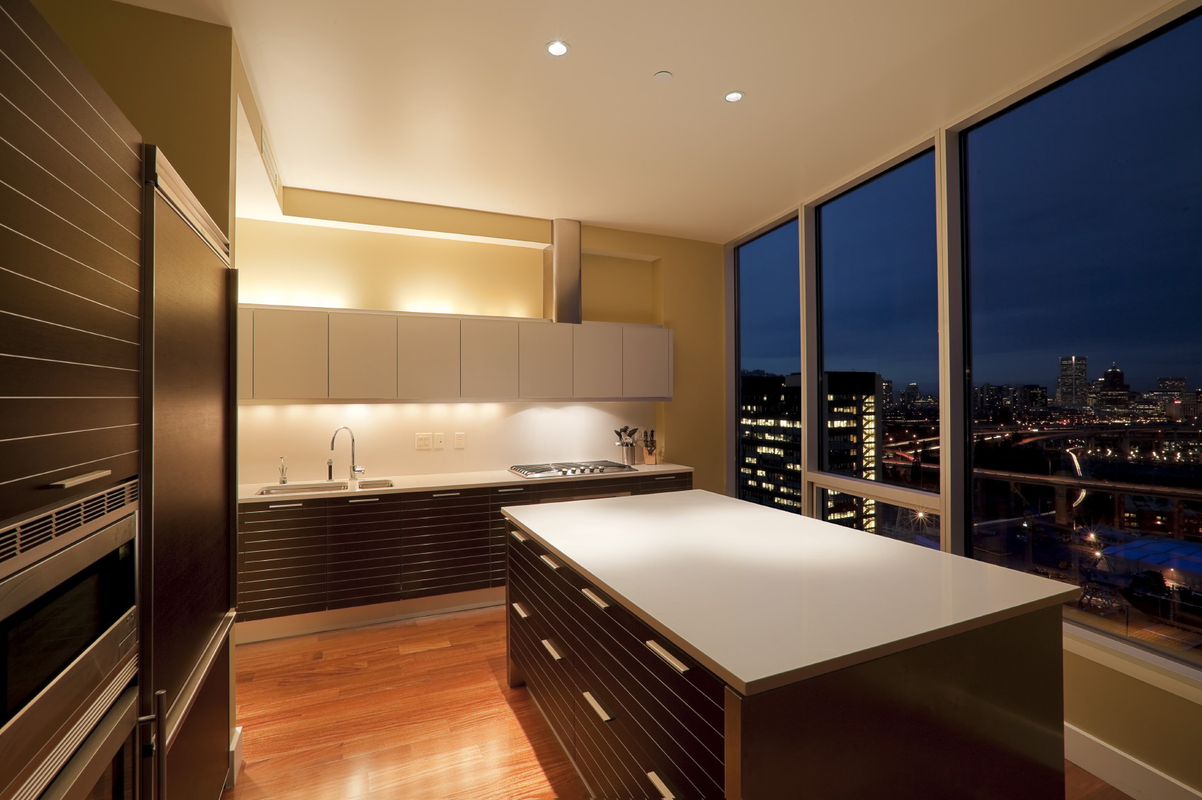 Unique modern touches like the horizontal lined cabinetry under glossy white upper cupboards in this kitchen featuring floor to ceiling view of cityscape next to large island.