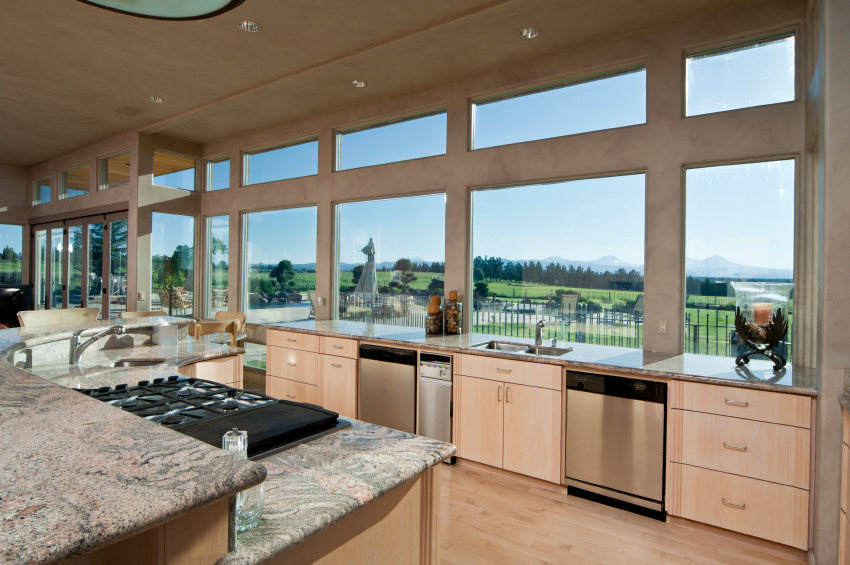 Salmon hued cabinetry over light natural wood flooring warm this kitchen with concrete walls and marble countertops. Exterior wall is nearly all windows, for maximum natural lighting.