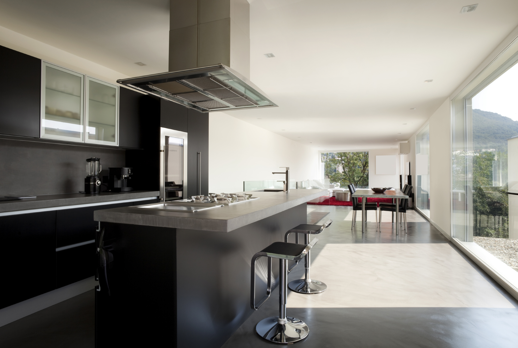 Lengthy kitchen features jet black cabinetry with slate grey countertops under large free-hanging hood vent, with dining and living areas in distant open space.