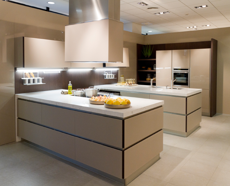Light beige tones cover the minimalist surfaces in this kitchen, with matching tile floor and under-cabinet lighting.