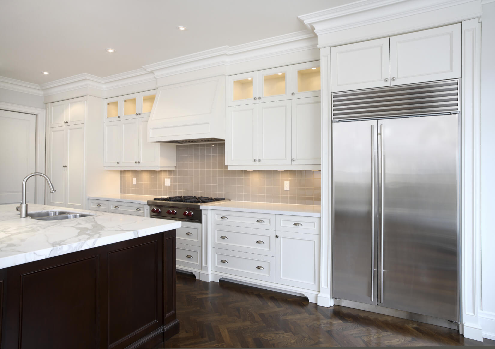 Kitchen features a traditional mix of colors, with natural wood flooring under white painted cabinetry. Marble countertop on island stands in contrast to dark wood siding.