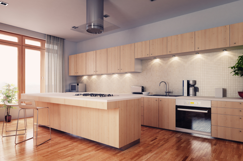 Here we have an example of natural materials used in modern configuration: warm hardwood flooring supports light wood minimalist cabinetry around white countertops and tile backsplash with under-cabinet lighting.