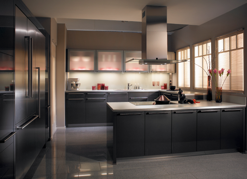 Dark hues throughout this kitchen are set off by embedded lighting and white countertops. Black cabinetry and aluminum appliances stand out.