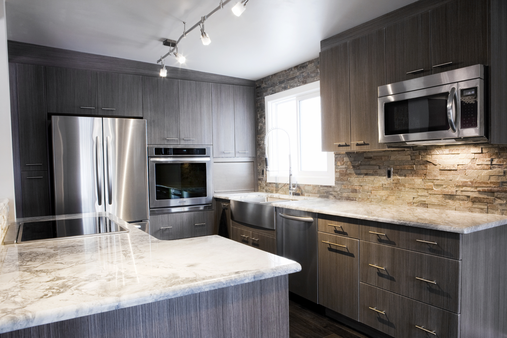 This cozy space is anchored by old fashioned brick backsplash wall and marble countertops. Grey natural wood contrasts with aluminum appliances over dark hardwood flooring.