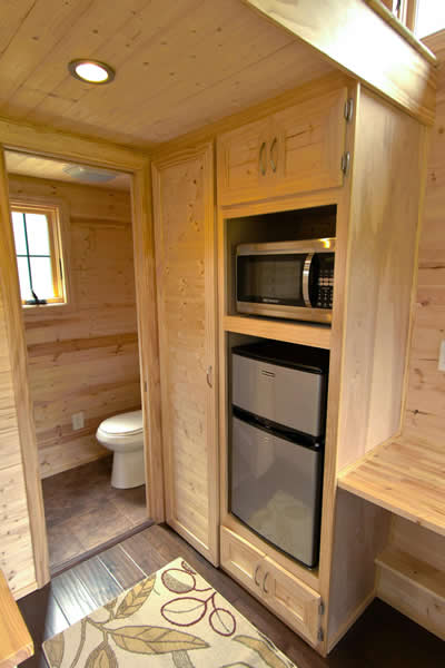 Kitchenette features compact refrigerator and microwave in built-in shelving, with bathroom in background.