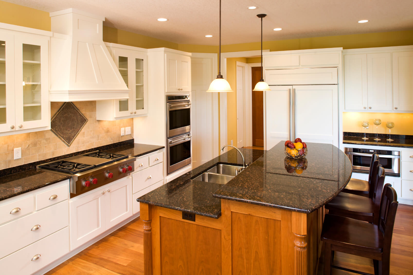Here we have another two-tiered island adding contrast to a kitchen with warm natural wood and dark marble countertop.