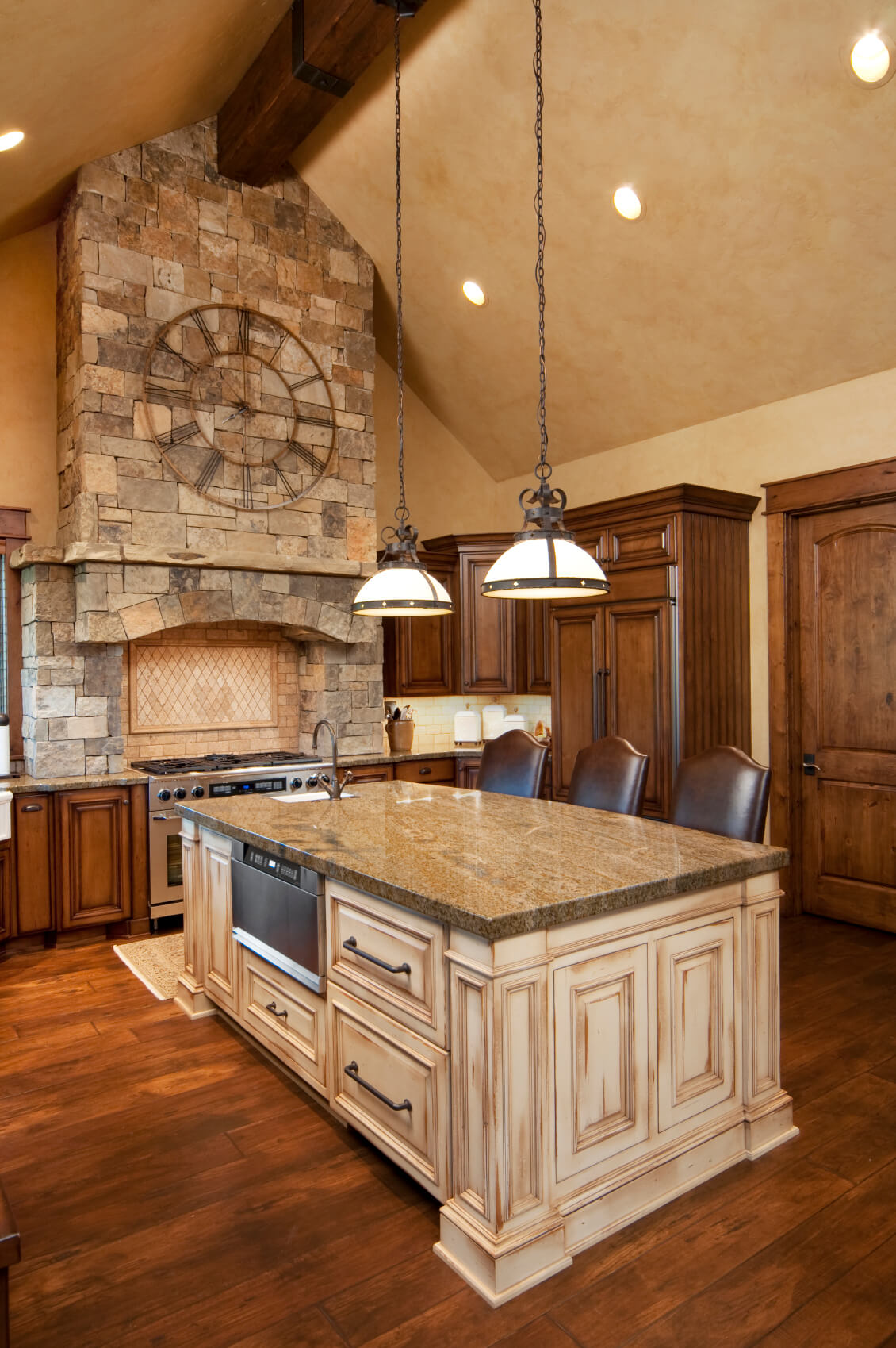 Rich, natural wood kitchen holds this large, contrasting light wood island at center, with built-in dishwasher, storage, and sink, across from dining seating.