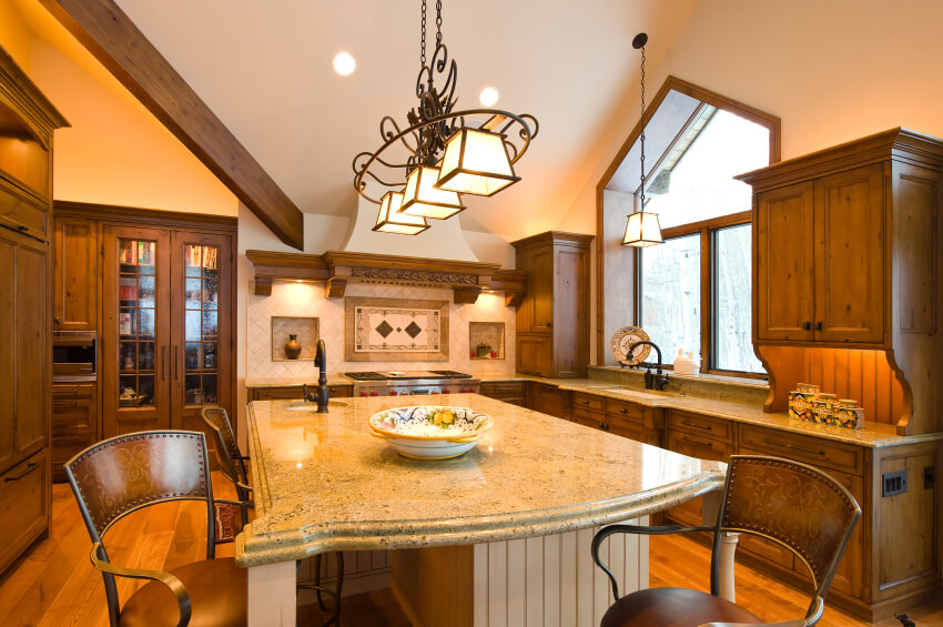 Large island doubling as dining table, with large overhang and carved wood legs. Light marble countertop matches with kitchen while white wood paneling adds contrast.