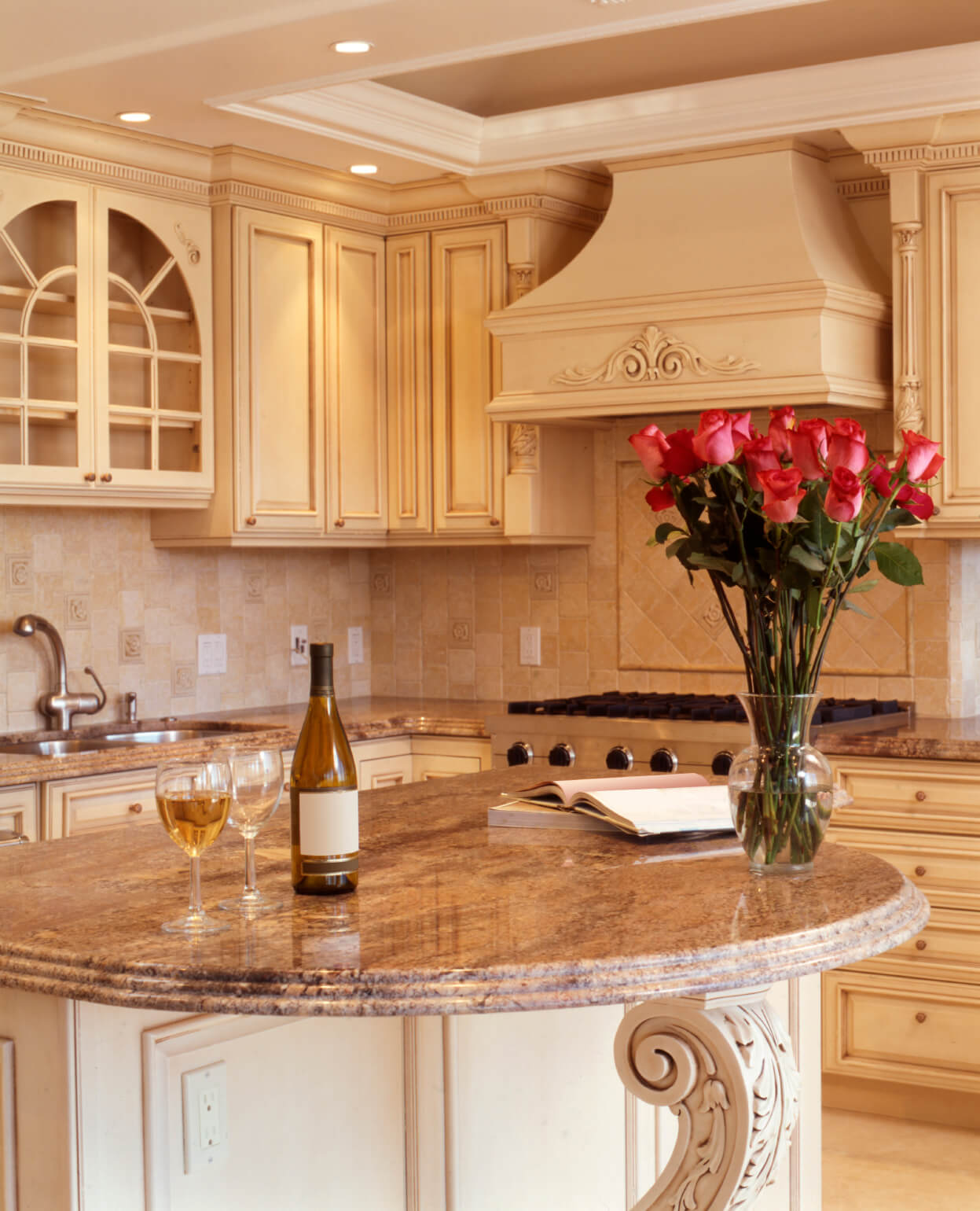 Lush beige tones throughout this kitchen, including filigreed wood island with rounded marble countertop.
