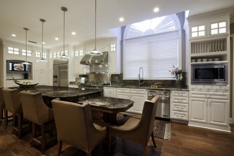 Comfortable, yet luxurious kitchen design with two-tiered kitchen island with very comfortable seating.  The dark island is offset with white cabinetry throughout the rest of  the kitchen.