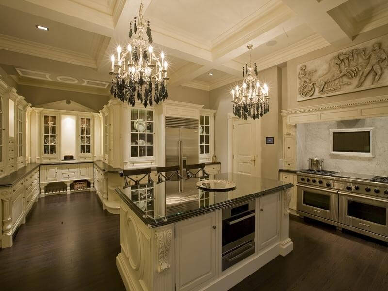Spacious white kitchen with dark flooring and countertops.  Custom cabinetry throughout providing a great deal of storage.