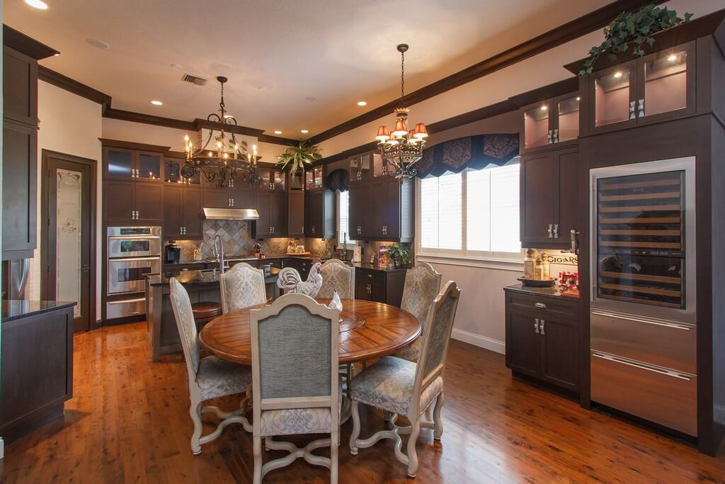 Expensive kitchen with elegant round dining table and chairs in  the kitchen.  Kitchen includes wine refrigerator and custom cabinets throughout.
