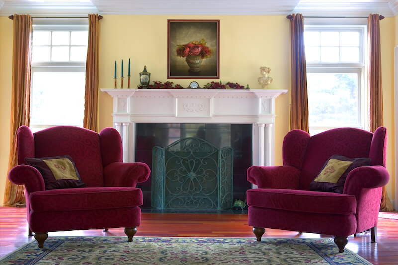 In front of a fireplace, these matching red armchairs with a subtle swirl pattern provide a satisfying pop of color in contrast to the white mantle. They're wide enough to curl up comfortably with a book next to the fire.