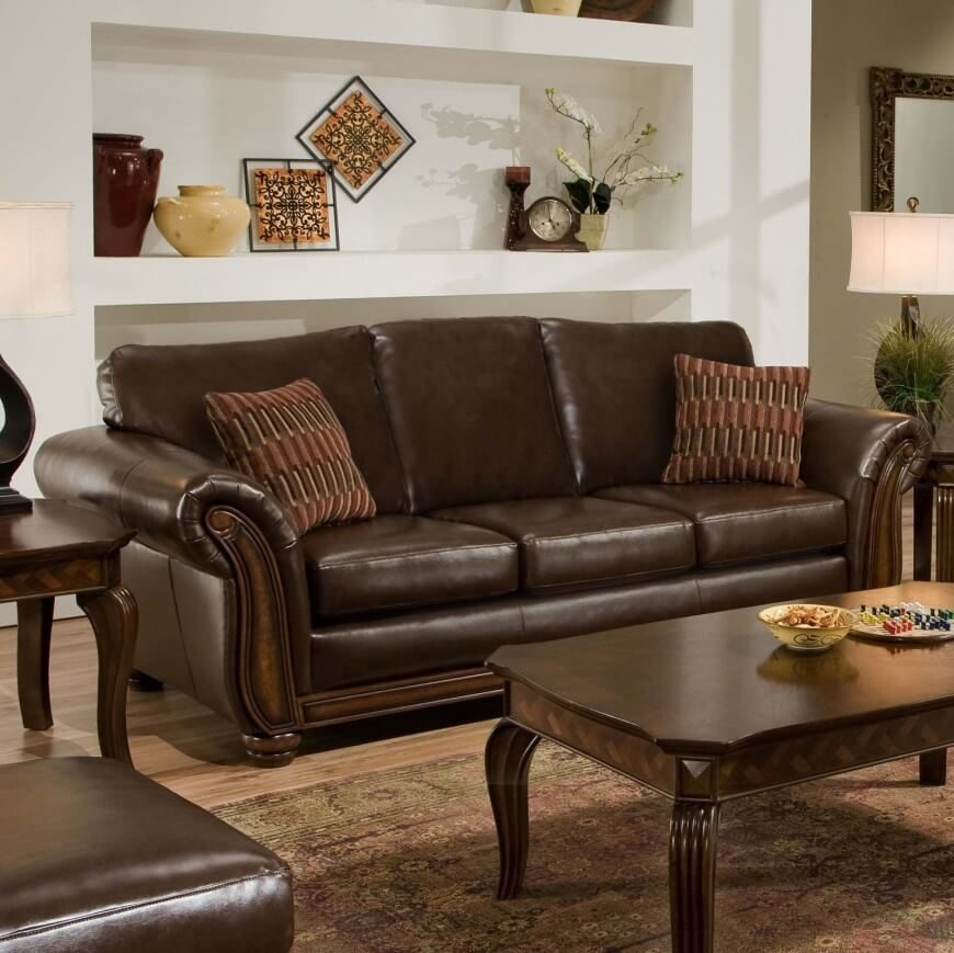 A sleek brown leather sofa with accent pillows. When paired with dark wooden tables, a lighter brown rug and light, neutral walls, the rich chocolate color stands out in an elegant way.