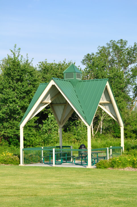 A tall gable roof in a bright green makes this public gazebo an easy structure to spot from a long ways away. The gazebo is furnished with a picnic table, chairs, and a trash can.