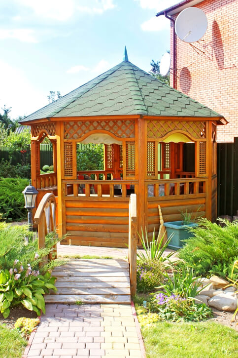 The lattice, log-cabin sides, and hexagonal roof shingles give this unique wooden gazebo an exotic look.