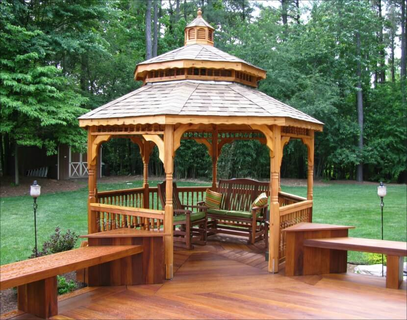 This cedar gazebo is attached to the side of a deck and overlooks the wooded backyard, including a shed tucked into the trees.
