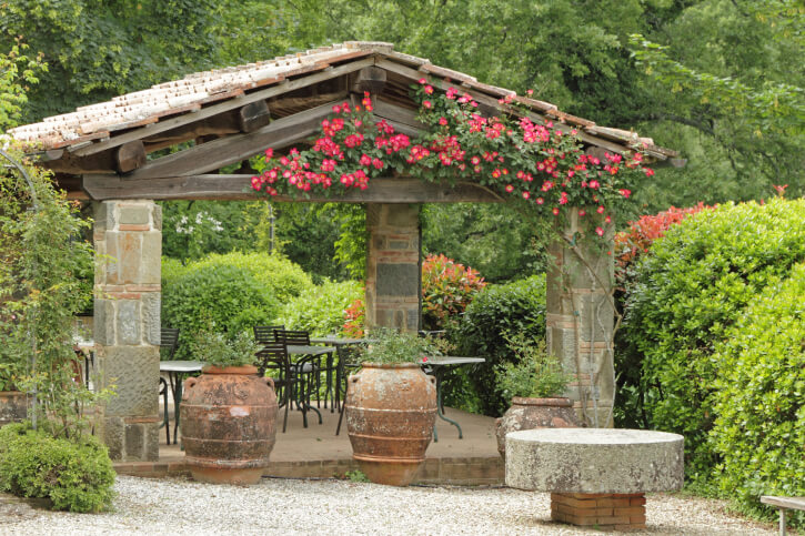 This is a great example of a custom gazebo made out of stone, which isn't exactly a common material. Trailing flowers up the supports gives this gazebo a huge pop of color.