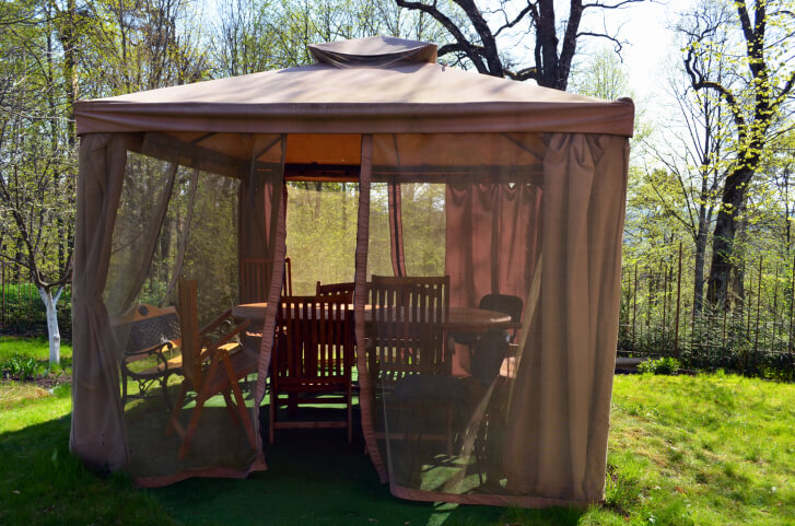 """Screened gazebos like this one have the option of curtains for privacy. Much like a tent, this gazebo has fabric """"walls."""""""