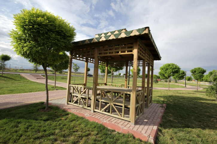 An eclectic square gazebo with clever details on the roof and a sunburst design on the sides. The structure is a nice spot to rest off the brick pathway.