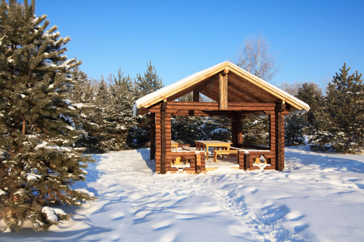 A log-cabin style gazebo is perfect on snowy days. This one has the feel of a high-end ski resort.