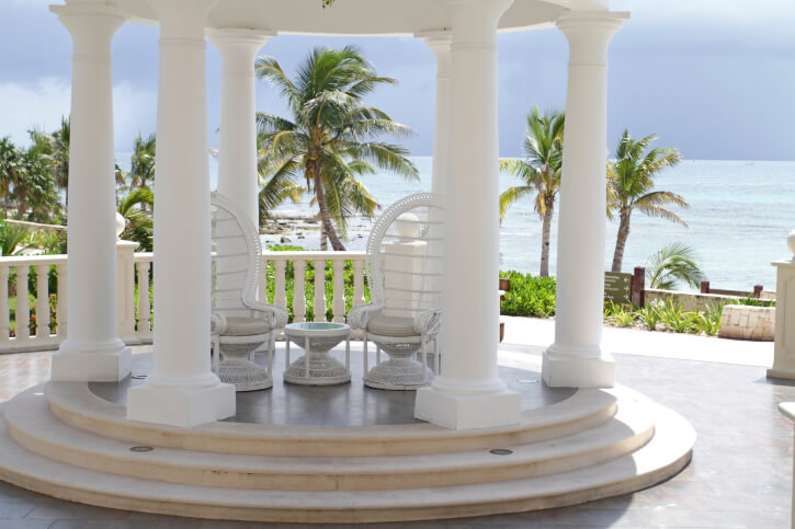 Another lovely round gazebo overlooking a tropical sea and palm trees. This style is small, so it only has room for a couple of chairs. This does, however, make for an intimate atmosphere.