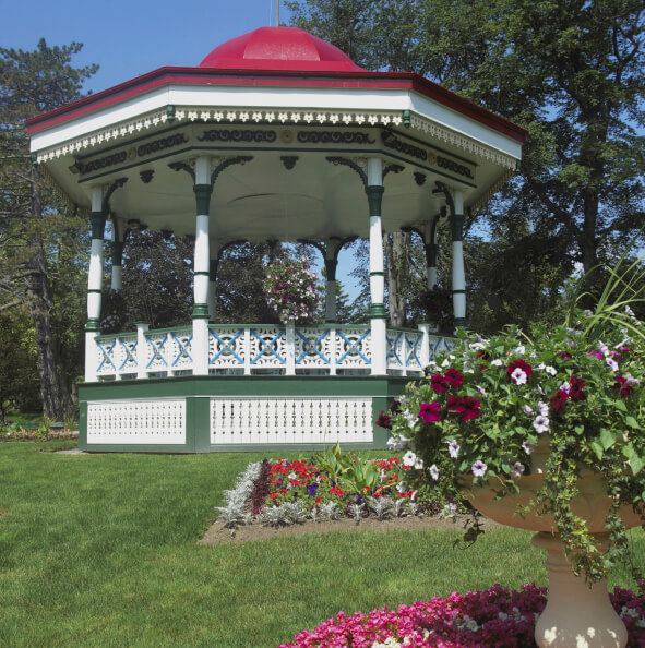 A colorful gazebo that is large enough to be used as a bandstand. The surrounding landscape is color matched to the paint job on the gazebo.