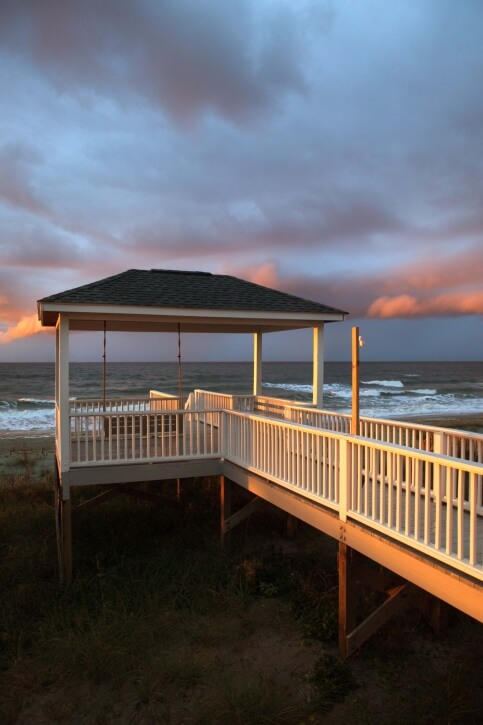 A hard top gazebo at the end of a long walkway over the dunes. The gazebo is equipped with a porch swing that looks out over the waves.