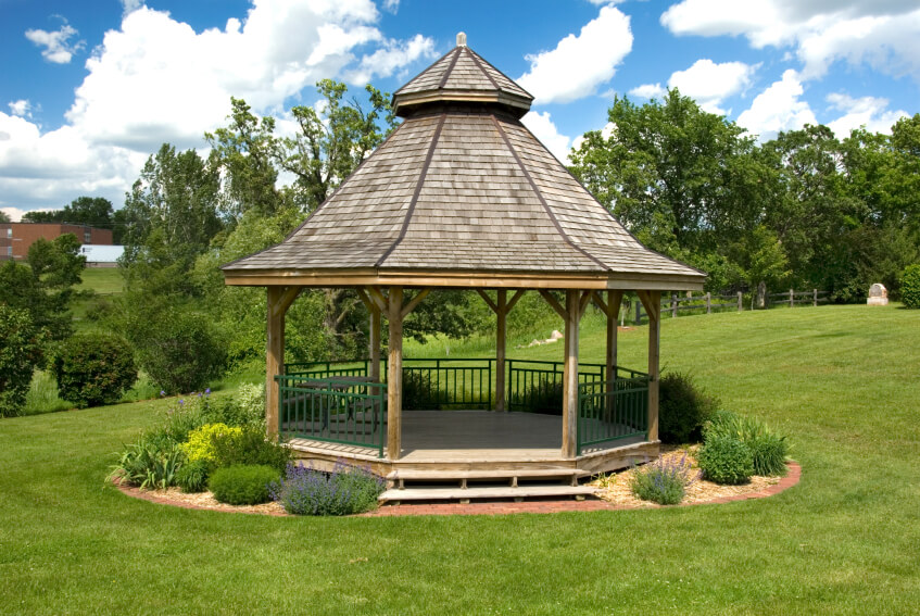 A large wooden gazebo with a two tiered roof, surrounded by shrubs and bushes. The simple landscaping gives this gazebo a pastoral feel.