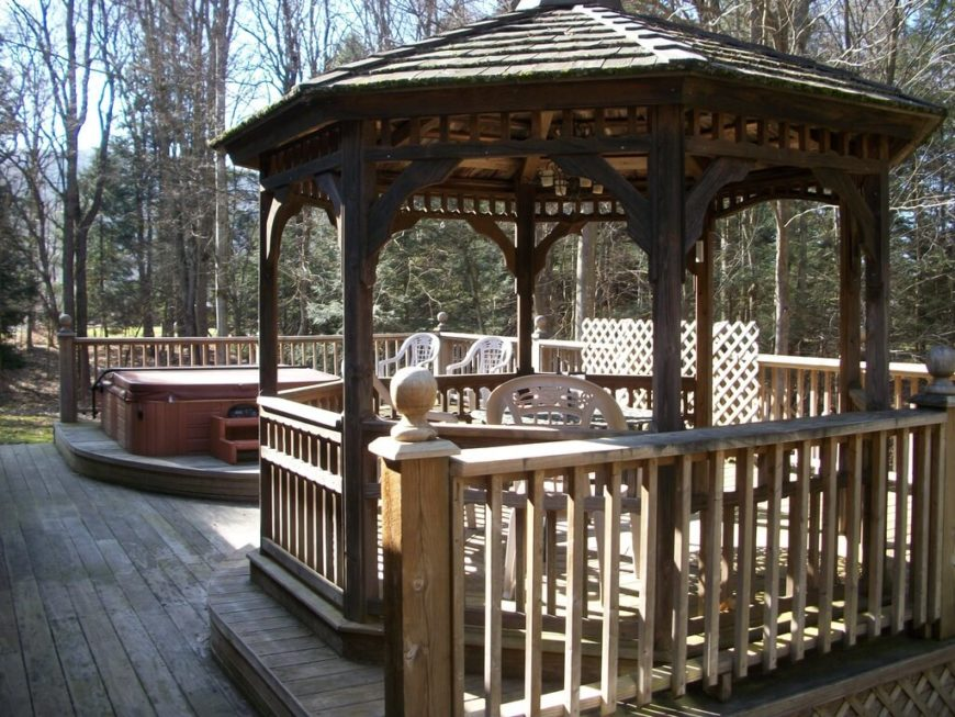 This gazebo is placed on its own wooden platform, raised up about a foot from the main deck. The hot tub across from it is given the same treatment