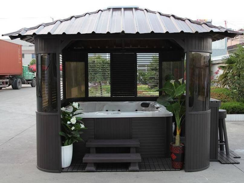This portable hot tub gazebo features a riveted roof, tinted glass windows, and enough extra space to add some plants or shelving for towels.
