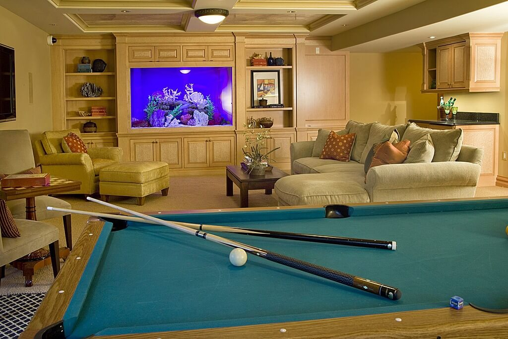 This man cave boasts a cozy sofa set and a wide screen TV, along with the classic billiards pool set on the carpet flooring.