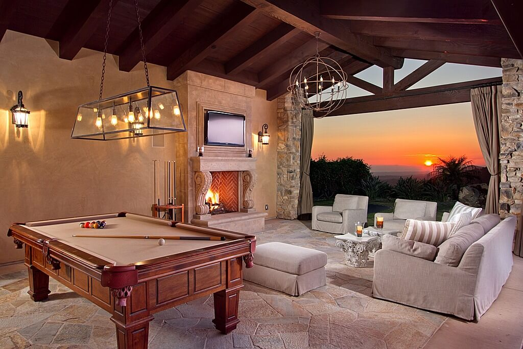 Large outdoor living space featuring a cozy sofa set with a fireplace along with a billiards pool lighted by a lovely pendant lighting set on the wooden vaulted ceiling.