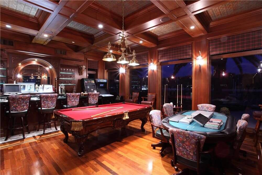 This game room boasts multiple gaming tables and arcade games along with a classy bar area, all under the elegant coffered ceiling with a beautiful ceiling and wall lights.