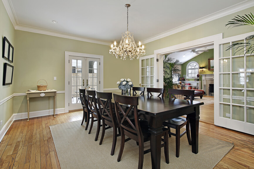 dark floor dining room   Large tropical-designed home with light yellow and white ...