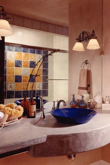 Close up of bathroom counter with blue vessel basin and tile work.