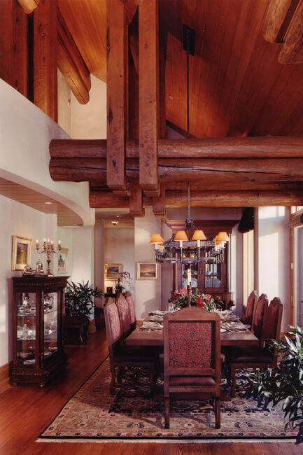 Formal dining room with seating for eight people. Dining furniture situated on large rug. China cabinet on the side of the room. Tall sloping ceiling above.