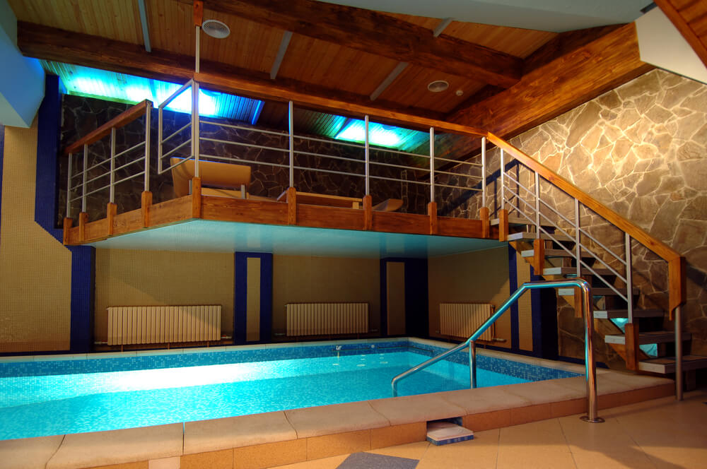 Indoor pool underground with loft patio area hanging over the pool. Ceiling is in wood and one wall in stone.