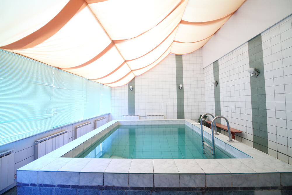 Small indoor pool with tile walls and soft illuminated fabric ceiling.