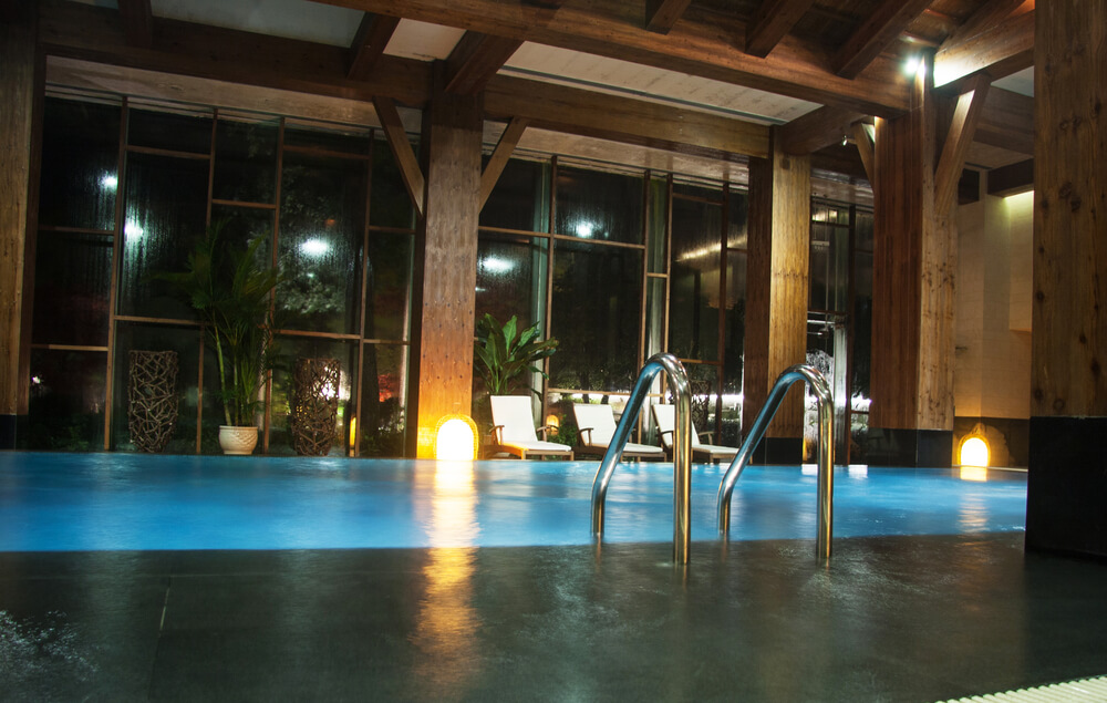 Large indoor pool room built with exposed wood beams throughout and extensive floor-to-ceiling windows.