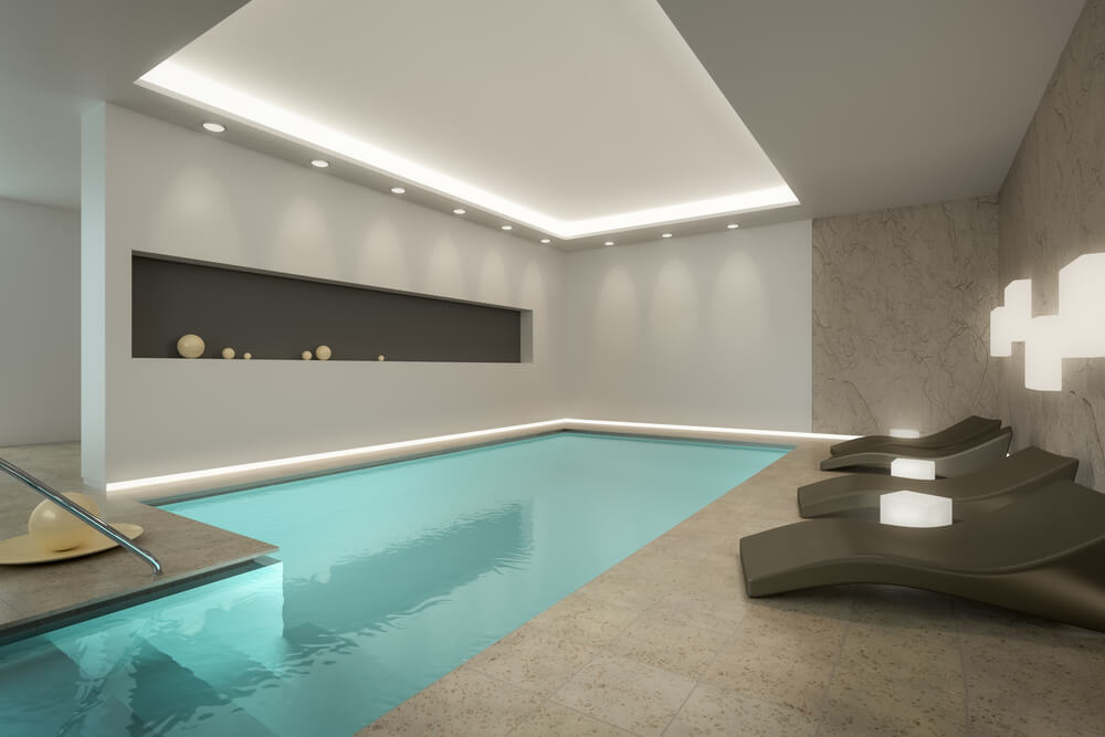 Modern indoor pool design with recessed ceiling and modern patio furniture.