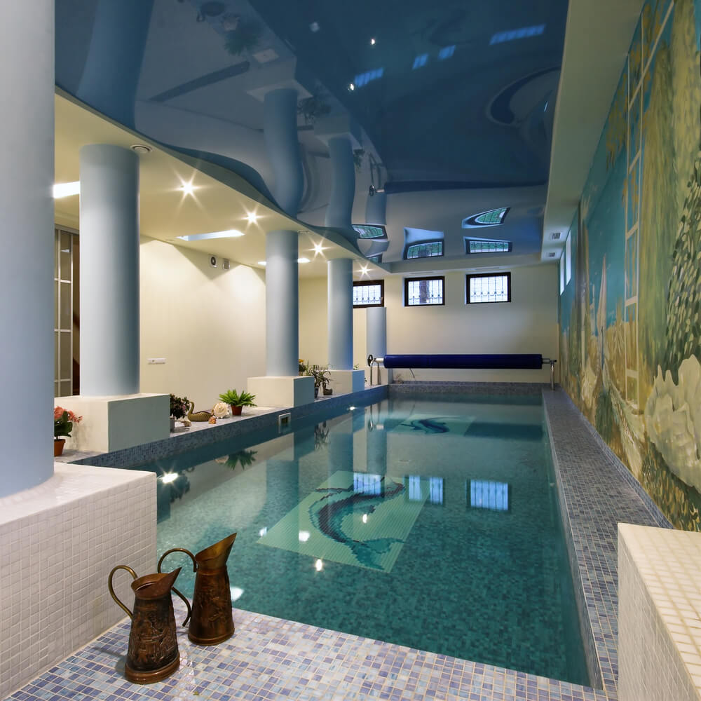 Large indoor pool room with white columns, shiny blue ceiling and large underwater mural.